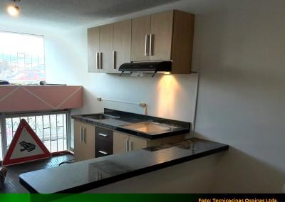 Cocina integral sencilla con barra auxiliar y cubierta en granito.