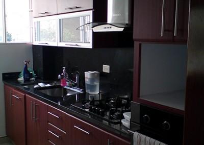 Cocina integral postformada, torre de hornos y cubierta en granito.