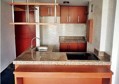 Cocina integral en formica con mesón en granito natural con mesón auxiliar en madecor