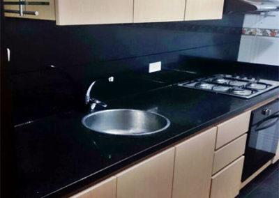 Cocina integral en formica con mesón en granito natural negro con poceta redonda
