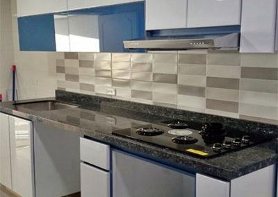 Cocina integral en pintura poliuretano con puertas superiores en vidrio azul