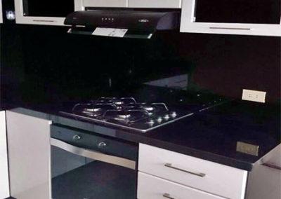 Cocina integral en pintura poliuretano con manijas, mesón y salpique en granito natural negro