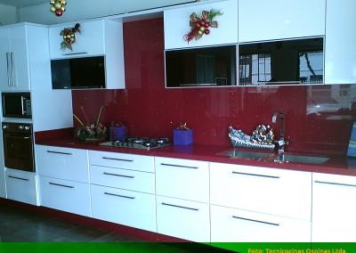 Cocina exhibición con puertas en vidrio y torre de hornos. Cubierta en quarztone