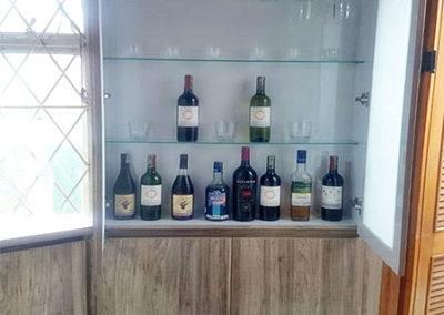 Mueble botellero en formica color madera enevejecida con entrepaños en vidrio