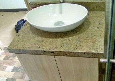Mueble de baño en formica tono madera claro con mesón en mármol café
