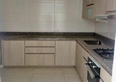 Cocina integral en formica en tono madera claro con mesón en granito natural marrón