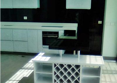 Cocina integral en pintura poliuretano blanca con mesón en granito natural negro y Quarztone blanco