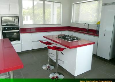 Cocina integral con perfil en aluminio, cubierta y barra en caesarstone.