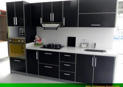 Cocina integral con torre de hornos, cubierta y salpique en caesarstone.