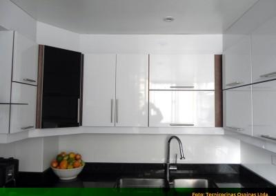 Cocina integral con puerta en vidrio, cenefa baja y cubierta en granito.